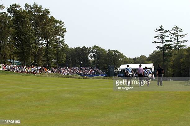 Davis Love III and Phil Mickelson walk up the fairway towards the green on the 18th hole during the third round of the Deutsche Bank Championship at...