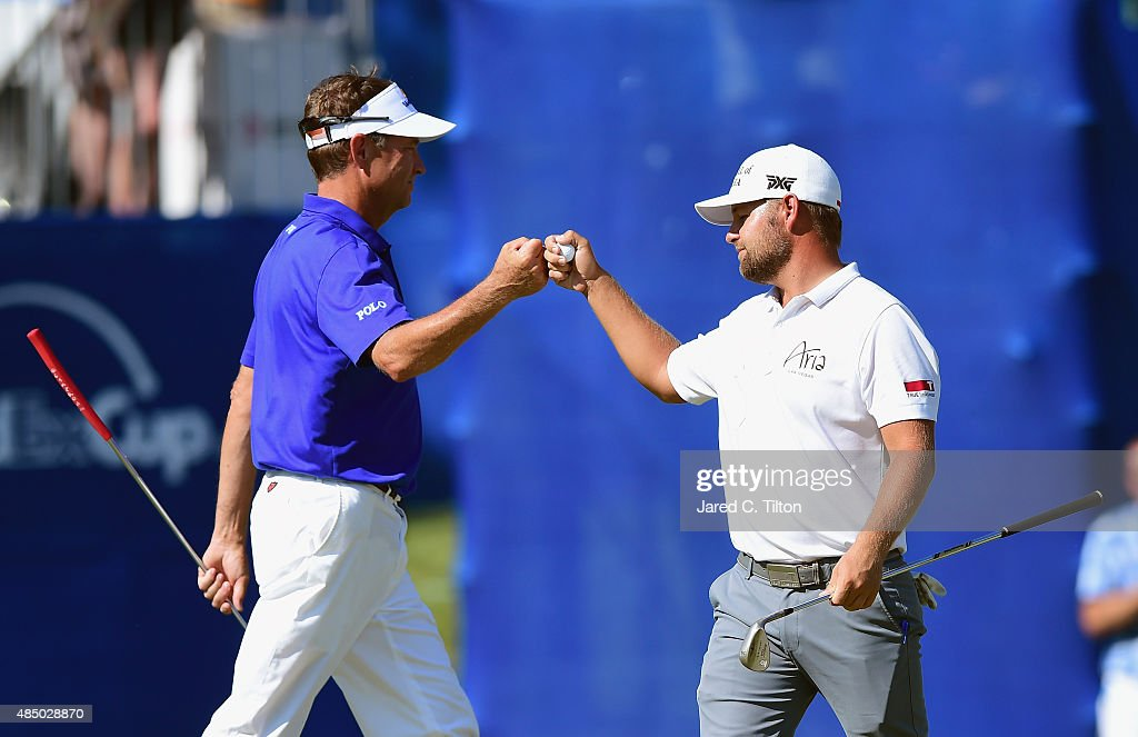 Davis Love III (left) congatulates Ryan Moore after Moore holed out for birdie from off of the green on the 17th hole during the final round of the Wyndham Championship at Sedgefield Country Club on August 23, 2015 in Greensboro, North Carolina.