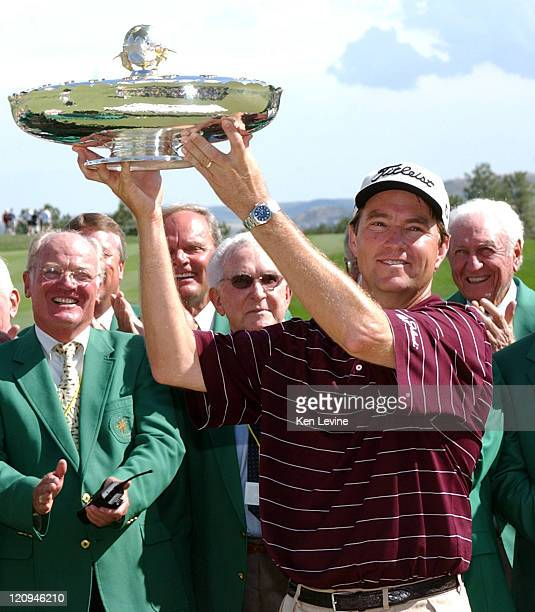 Davis Love III holds aloft the trophy for winning the International at Castle Pines Colorado by a 12 point margin Behind Love are members of the...