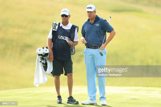 Davis Love IV of the United States and caddy Davis Love III lines up a putt on the fourth hole during the first round of the 2017 US Open at Erin...