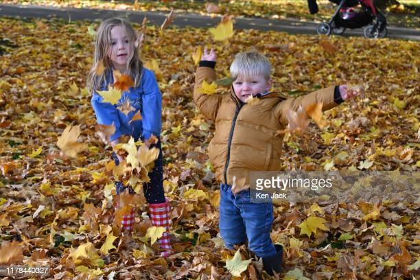 Davis Morrison and sister Isla Rose from Glasgow have fun among the autumn leaves beside Linlithgow Loch on the day the clocks changed from British...