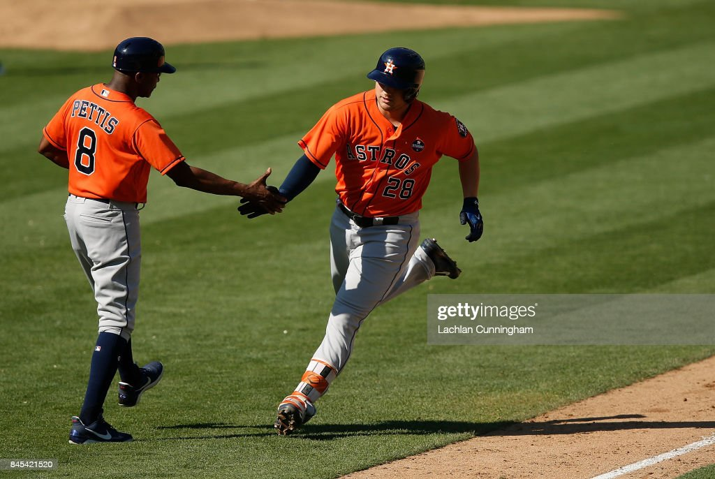 J.D. Davis #28 of the Houston Astros celebrates with Third Base Coach Gary Pettis #8 of the Houston Astros after hitting a solo home run in the eighth inning against the Oakland Athletics at Oakland Alameda Coliseum on September 10, 2017 in Oakland, California.