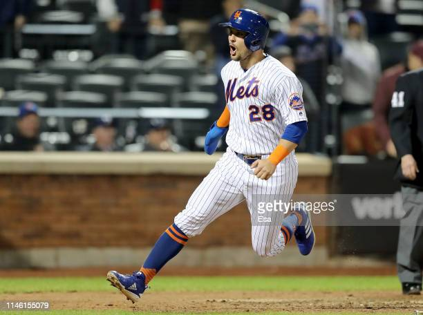 D Davis of the New York Mets celebrates after he scored the game winning run in the bottom of the 10th inning against the Cincinnati Reds at Citi...