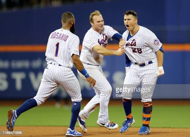 D Davis of the New York Mets celebrates his first career walk off single with teammates Amed Rosario and Pete Alonso in the 10th inning against the...