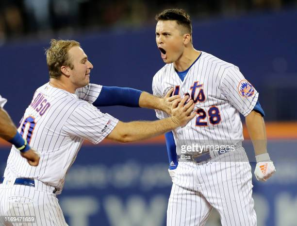 D Davis of the New York Mets celebrates his first career walk off single with teammate Pete Alonso in the 10th inning against the Cleveland Indians...