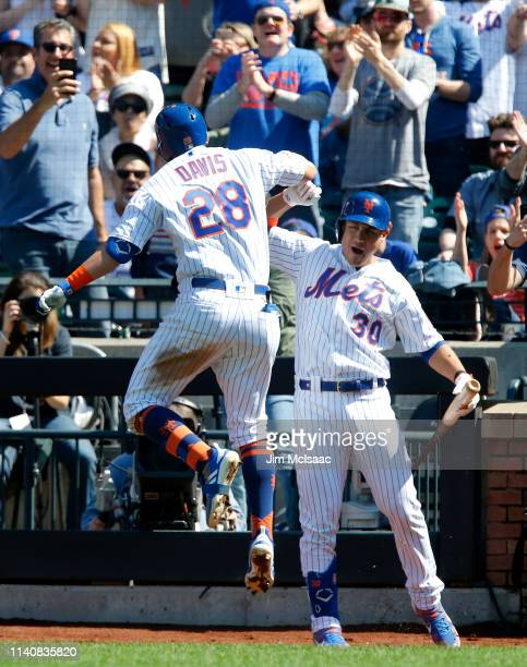 D Davis of the New York Mets celebrates his fourth inning home run against the Washington Nationals with teammate Michael Conforto at Citi Field on...