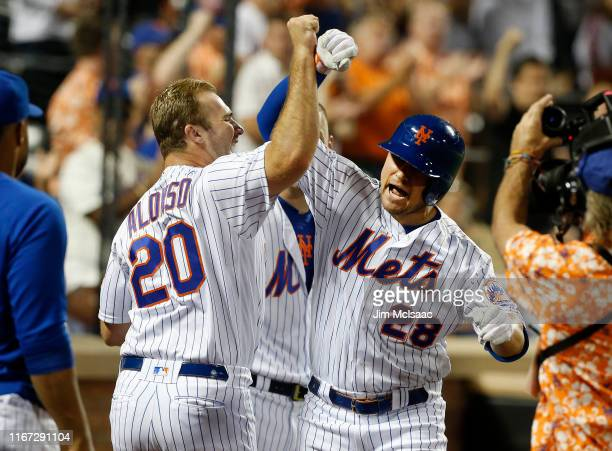 D Davis of the New York Mets celebrates his fourth inning home run against the Washington Nationals with teammate Pete Alonso at Citi Field on August...