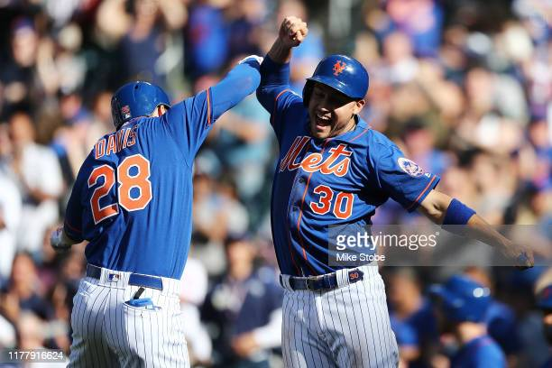 D Davis of the New York Mets celebrates with Michael Conforto after hitting a tworun home run to center field in the first inning against the Atlanta...