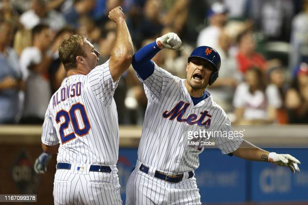 D Davis of the New York Mets celebrates with Pete Alonso after hitting a home run to right field in the fourth inning against the Washington...