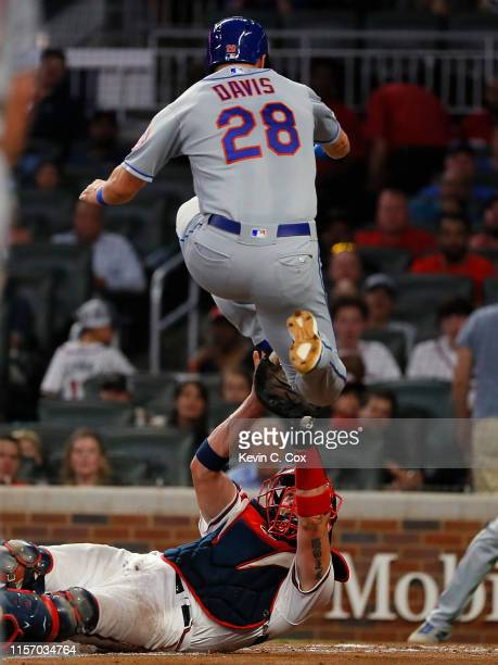 D Davis of the New York Mets is tagged out at home as he leaps over Tyler Flowers of the Atlanta Braves in the sixth inning at SunTrust Park on June...