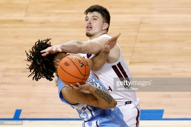 Davis of the North Carolina Tar Heels is fouled by Hunter Cattoor of the Virginia Tech Hokies as he drives to the basket during the second half of...