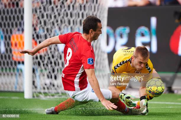 Davit Skhirtladze of Silkeborg IF and Goalkeeper Aleksandar Jovanovic of AGF Aarhus compete for the ball during the Danish Alka Superliga match...