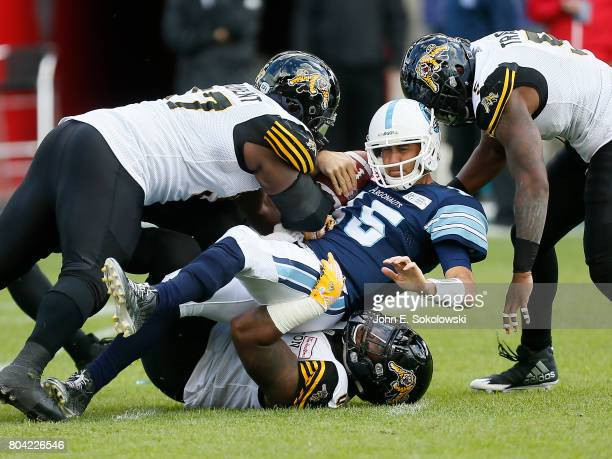 Davon Coleman and Ted Laurent and Adrian Tracy of the Hamilton TigerCats sack Ricky Ray of the Toronto Argonauts during a CFL game at BMO Field on...