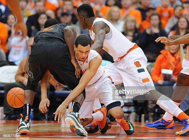 Davon Reed of the Miami Hurricanes Tyler Ennis and Jerami Grant of the Syracuse Orange battle for a loose ball during the second half at the Carrier...