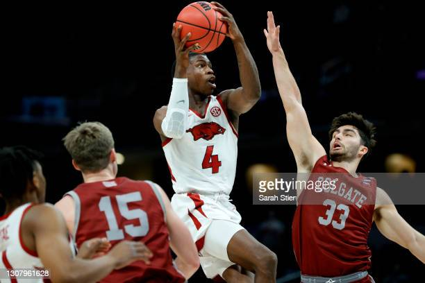 Davonte Davis of the Arkansas Razorbacks drives to the basket against Oliver Lynch-Daniels of the Colgate Raiders during the first half in the first...