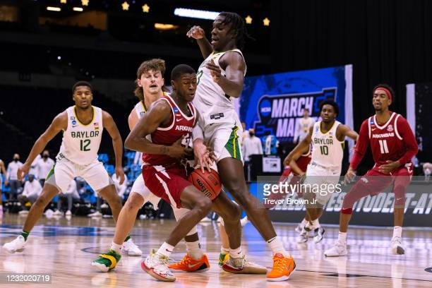 Davonte Davis of the Arkansas Razorbacks loses possession of the ball while while attempting to drive past Matthew Mayer and Jonathan Tchamwa...