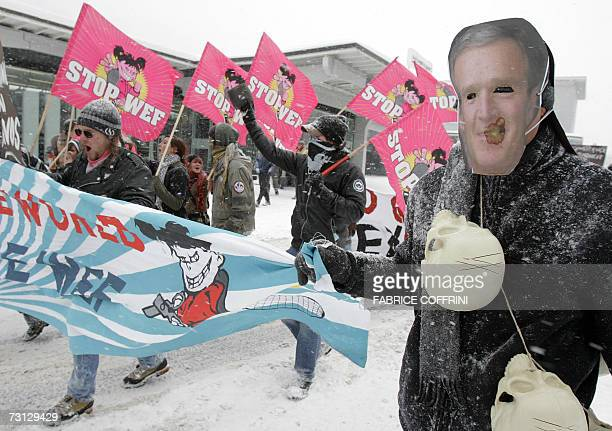 A demonstrator wearing a mask depicting US President George W Bush walks 27 January 2007 during a demonstration against the Annual Meeting of the...