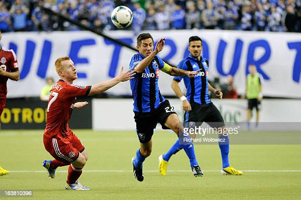 Davy Arnaud of Montreal Impact heads the ball past Richard Eckersley of Toronto FC during the MLS game at the Olympic Stadium on March 16 2013 in...