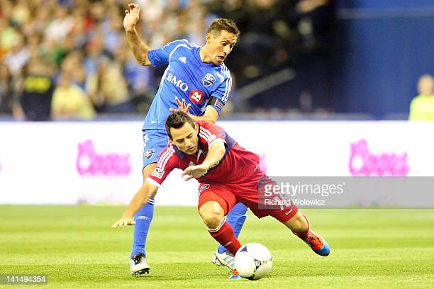 Davy Arnaud of the Montreal Impact trips Marco Pappa of the Chicago Fire during the MLS match at the Olympic Stadium on March 17 2012 in Montreal...