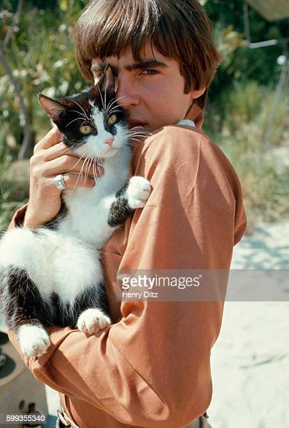 Davy Jones holds a black and white cat on the set of The Monkees TV show