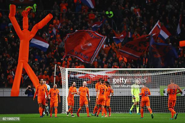 Davy Klaassen of the Netherlands celebrates with team mates as he scores their first goal from a penalty during the international friendly match...