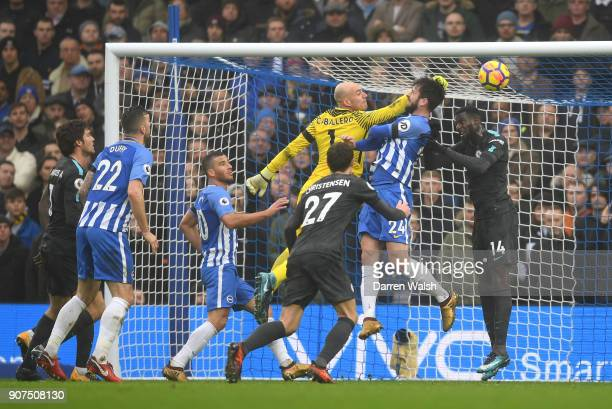 Davy Propper of Brighton and Hove Albion heads wide under pressure from Willy Caballero of Chelsea during the Premier League match between Brighton...