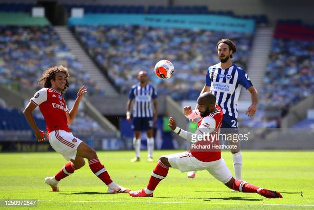Davy Propper of Brighton and Hove Albion is challenged by Matteo Guendouzi and Alexandre Lacazette of Arsenal during the Premier League match between...