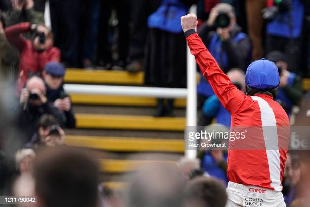 Davy Russell celebrates after riding Envoi Allen to win The Ballymore Novices' Hurdle on Ladies Day at Cheltenham Racecourse on March 11 2020 in...