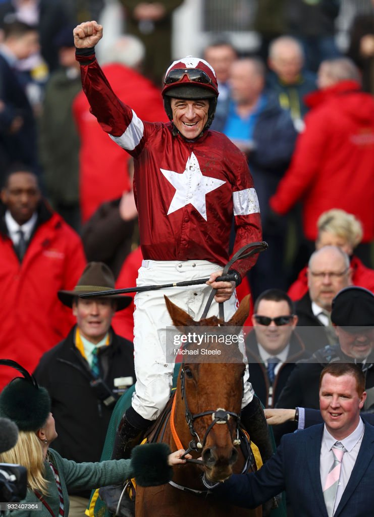 Davy Russell celebrates on Balko Des Flos as they are lead into the winners enclosure after victory in the Ryanair Chase at Cheltenham Racecourse on March 15, 2018 in Cheltenham, England.