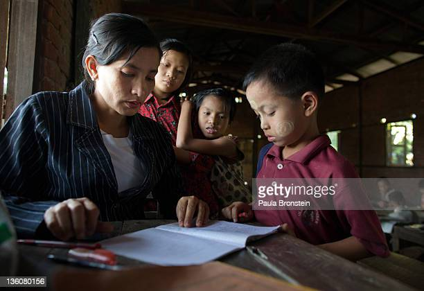 Daw Khin Markyu marks papers during a class at a small government run school December 14 2011 in Waw township Myanmar The education system is based...