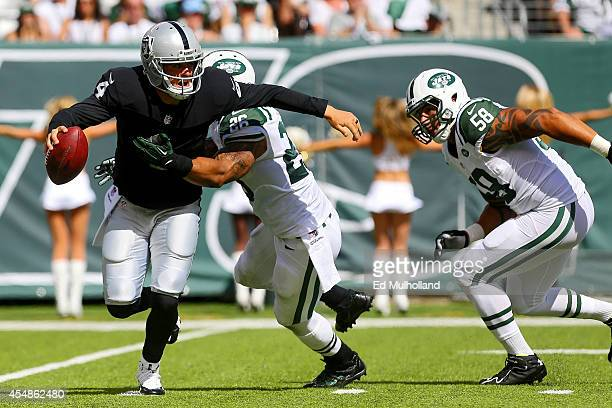 Dawan Landry and Jason Babin of the New York Jets sack Derek Carr of the Oakland Raiders during the third quarter at MetLife Stadium on September 7...