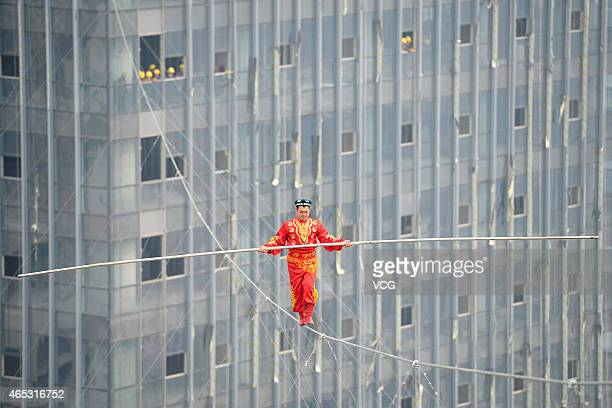 Dawazi performer Saimaiti Aishan walks on a tightrope 190 meters above the ground during a performance at Wanda Center on March 5 2015 in Taiyuan...