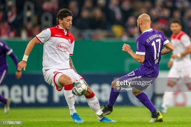 Dawid Kownacki of Fortuna Duesseldorf and Philipp Riese of Erzgebirge Aue battle for the ball during the DFB Cup second round match between Fortuna...