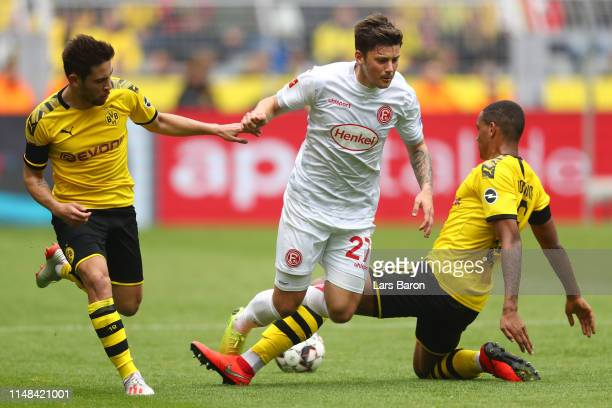 Dawid Kownacki of Fortuna Duesseldorf is challenged by Raphael Guerreiro and Manuel Akanji of Borussia Dortmund during the Bundesliga match between...