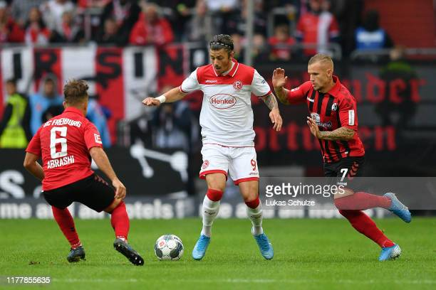 Dawid Kownacki of Fortuna Dusseldorf is challenged by Amir Abrashi and Jonathan Schmid of Sport-Club Freiburg during the Bundesliga match between...