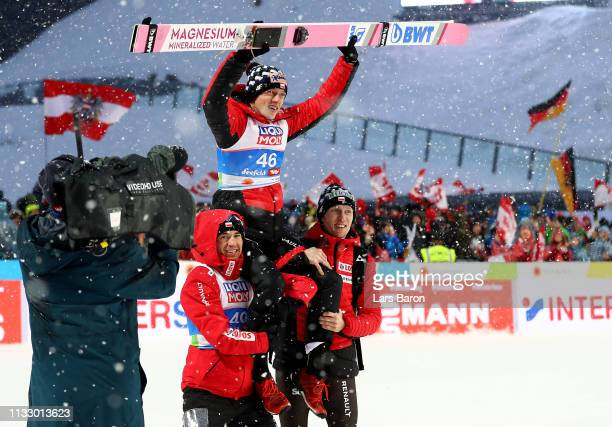 Dawid Kubacki of Poland celebrate with his team mates after he wins the gold medal in the ski jumping Men's HS109 final round during the 2019 FIS...