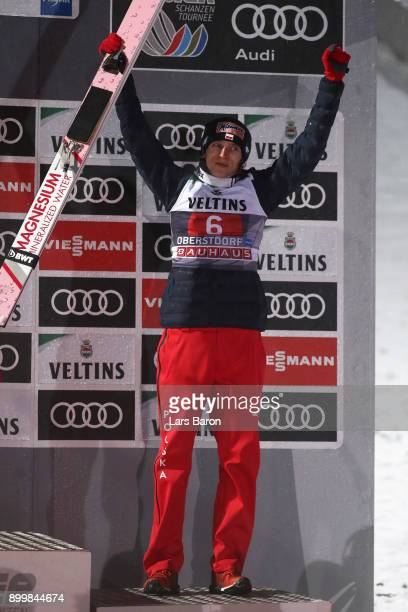 Dawid Kubacki of Poland celebrates his third place on the podium after the FIS Nordic World Cup on day 2 of the Four Hills Tournament ski jumping...