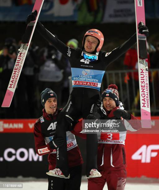 Dawid Kubacki of Poland celebrates winning after his second jump with Piotr Zyla and Kamil Stoch during the 68th FIS Nordic World Cup Four Hills...