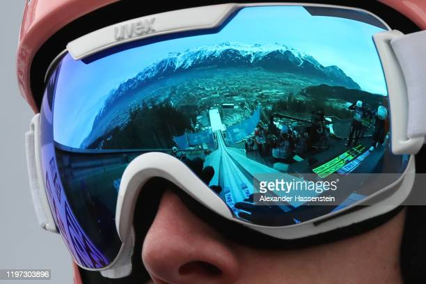Dawid Kubacki of Poland looks on prior to a during a training jump whilst the mountains Alpenkette is reflected in his ski googles during the 68th...