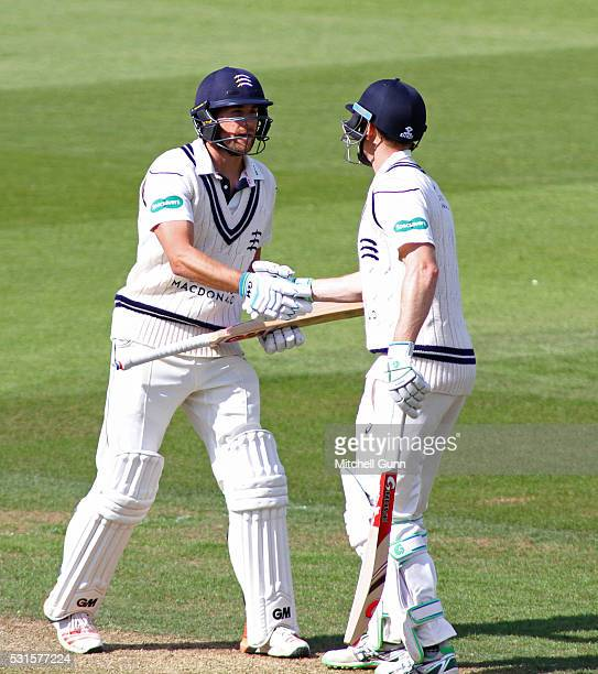 Dawid Malan celebrates scoring a half century with Adam Voges of Middlesex during the Specsavers County Championship Division One match between...
