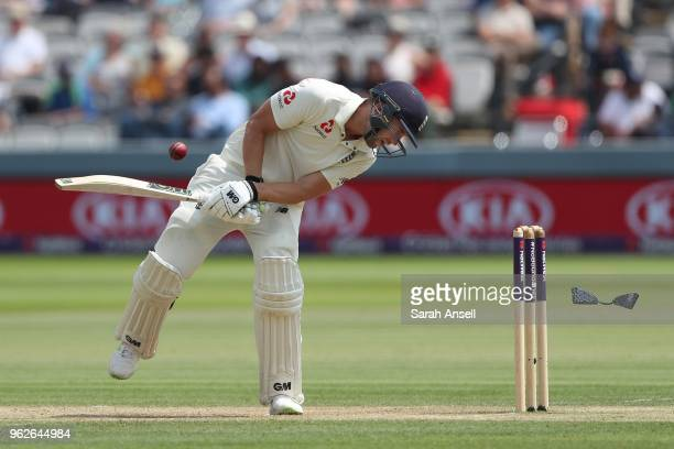 Dawid Malan of England is hit on the helmet part of which separates and narrowly misses the stumps on day 3 of the First NatWest Test match between...