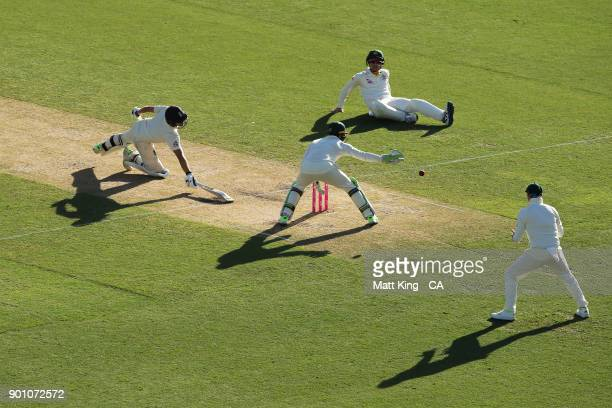 Dawid Malan of England slides in to avoid a runout chance by Cameron Bancroft of Australia during day one of the Fifth Test match in the 2017/18...