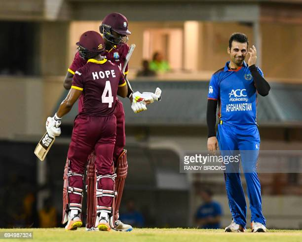 Dawlat Zadran of Afghanistan watch as Shai Hope and Jason Holder of West Indies celebrate winning the 2nd ODI match between West Indies and...