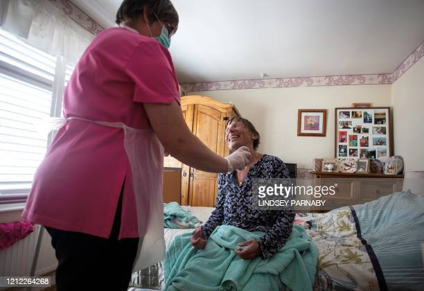 Dawn, a carer from Elite Care wears PPE as she tends to her client Tina during a home visit in Scunthorpe, northern England on May 8, 2020. - Tina...