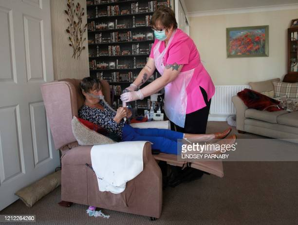 Dawn, a support staff member from Elite Care wears PPE as she tends to her client Tina during a home visit in Scunthorpe, northern England on May 8,...