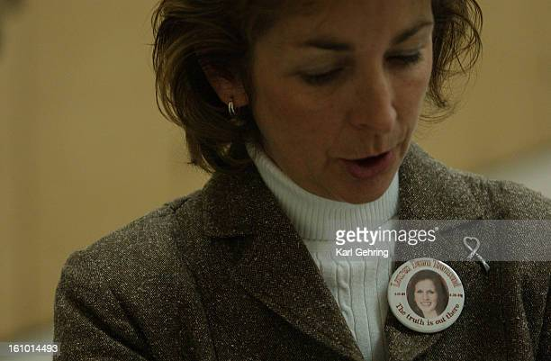 """Dawn Anna wore a button Thursday with a photo of her daughter, Columbine victim, Lauren Townsend on it with the phrase """"The truth is out there.""""..."""