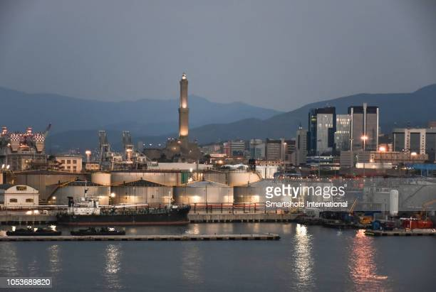 dawn at genoa's commercial port with lanterna lighthouse illuminated on background in genoa, italy - genova foto e immagini stock
