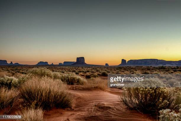 dawn at monument valley tribal park with beautiful desert sand in front of the majestic mitten bluffs of the tribal park - southwest usa stock pictures, royalty-free photos & images