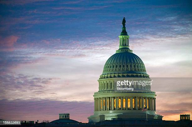 Dawn breaks at the US Capitol in Washington DC US on Monday Dec 31 2012 US lawmakers hurtled toward a midnight deadline to avert hundreds of billions...