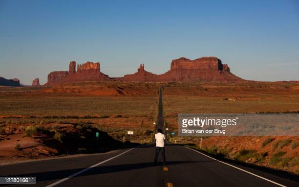 "Dawn breaks over sandstone formations as a man takes a photo at popular tourist stop dubbed ""Forrest Gump Hill"", the spot where the fictional movie..."